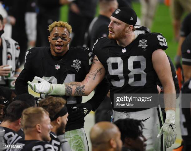 Strong safety Johnathan Abram and defensive end Maxx Crosby of the Las Vegas Raiders talk to teammates on the bench in the second half of their game...