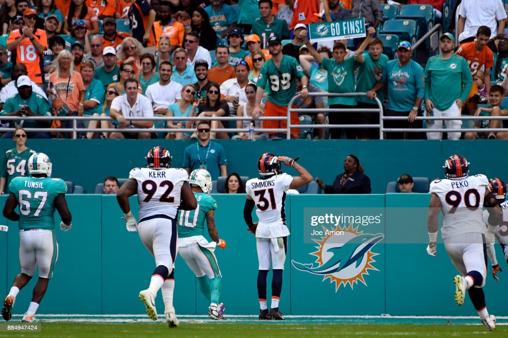 Strong safety Justin Simmons #31 of the Denver Broncos gives the Mile High Salute after he intercepts a ball for a touchdown late in the 3rd quarter to make the score 19-9 the Miami Dolphins at Hard Rock Stadium in Miami Gardens, Florida December 3, 2017.