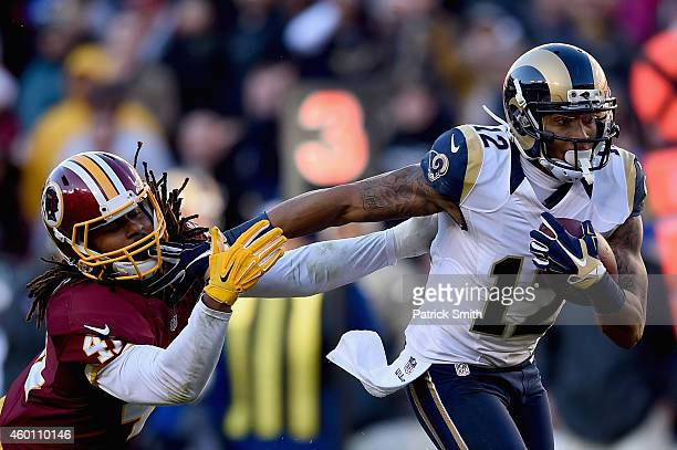 Strong safety Phillip Thomas of the Washington Redskins is stiff armed by wide receiver Stedman Bailey of the St Louis Rams in the third quarter of a...
