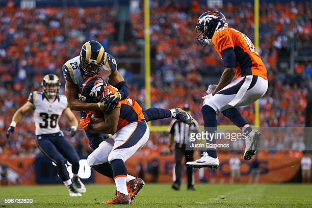 Strong safety TJ McDonald of the Los Angeles Rams tackles running back CJ Anderson of the Denver Broncos as Emmanuel Sanders and Cody Davis look on...