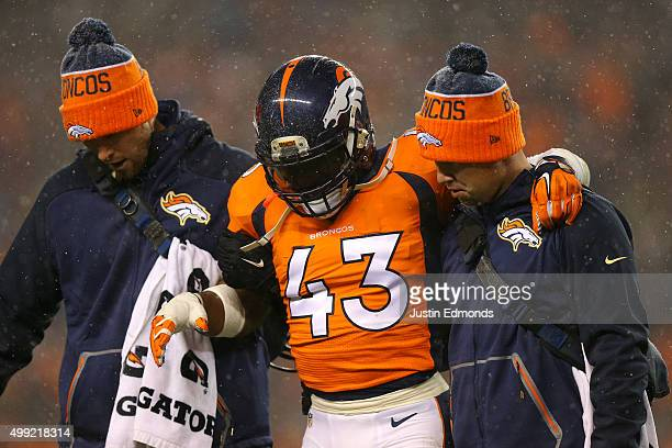 Strong safety TJ Ward of the Denver Broncos is helped off of the field after an injury against the New England Patriots at Sports Authority Field at...