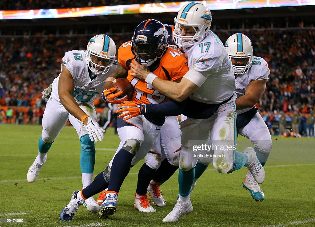 Strong safety T.J. Ward #43 of the Denver Broncos is tackled out of bounds by quarterback Ryan Tannehill #17 of the Miami Dolphins after a fourth quarter interception during a game at Sports Authority Field at Mile High on November 23, 2014 in Denver, Colorado.