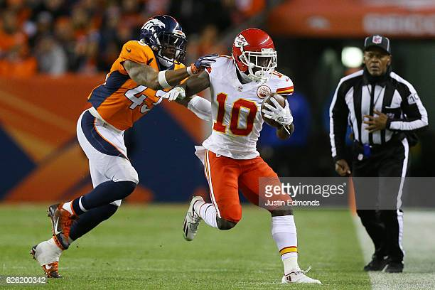 Strong safety TJ Ward of the Denver Broncos pushes wide receiver Tyreek Hill of the Kansas City Chiefs out of bounds in the first quarter of the game...