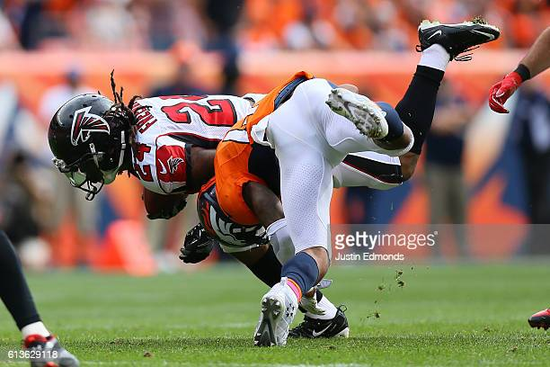 Strong safety TJ Ward of the Denver Broncos tackles running back Devonta Freeman of the Atlanta Falcons after a reception in the first quarter of the...