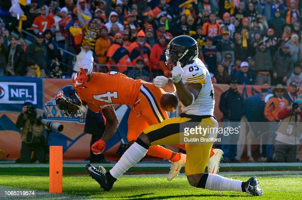 Strong safety Will Parks of the Denver Broncos forces a fumble by tight end Xavier Grimble of the Pittsburgh Steelers near the end zone resulting in...
