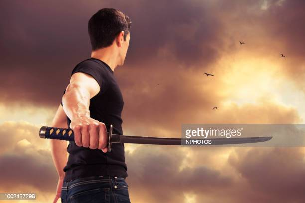 strong samurai and sword standing with dramatic evening sky - sword stock pictures, royalty-free photos & images