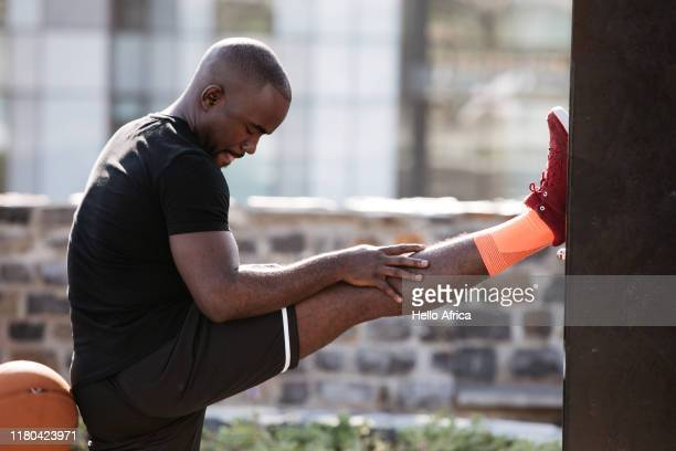 strong sportsman stretching out his hamstring with leg up - warming up stock pictures, royalty-free photos & images
