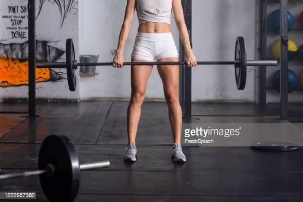 ジムで重量を持ち上げる強いスポーツウーマン - ランニングショートパンツ ストックフォトと画像