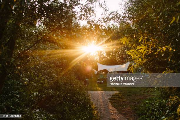 strong sunset backlight from behind a camping tent. - kamperen stock pictures, royalty-free photos & images
