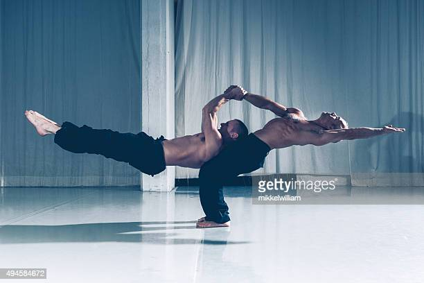 strong teamwork with two acrobats supporting each other - acrobatic activity stock photos and pictures