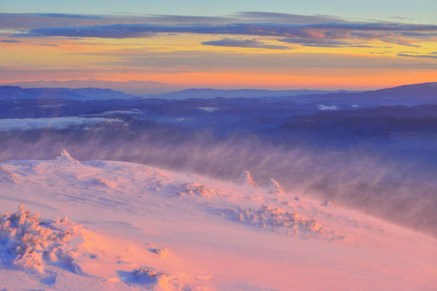 Strong wind blowing snow on a mountain peak at sunrise. Amazing sky wirh clouds over the valley