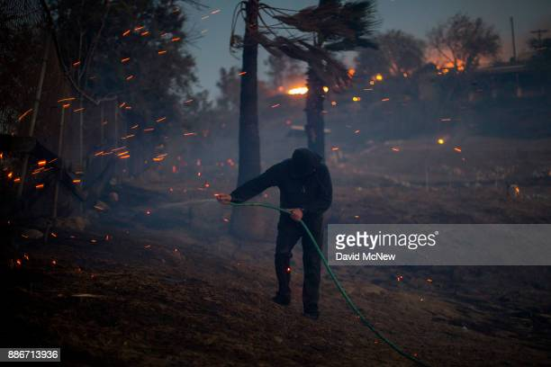 A strong wind blows embers around a resident hosing his burning property during the Creek Fire on December 5 2017 in Sunland California Strong Santa...