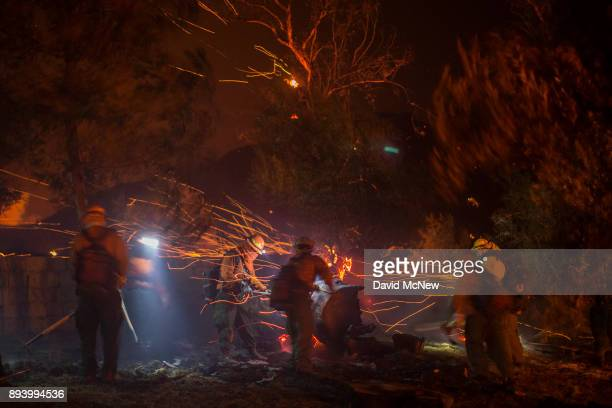 A strong wind blows embers around inmate firefighters putting out hot spots at the Thomas Fire on December 16 2017 in Montecito California The...