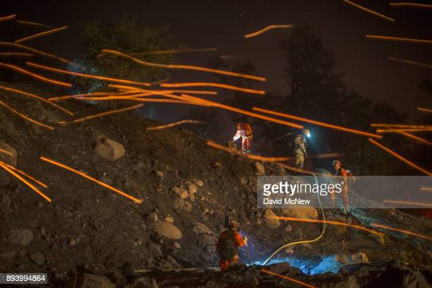 A strong wind blows embers past inmate firefighters putting out hot spots at the Thomas Fire on December 16 2017 in Montecito California The National...