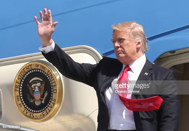 A strong wind blows President Donald Trump's tie as he steps off of Air Force One at Orlando International Airport for a visit to St Andrew Catholic...