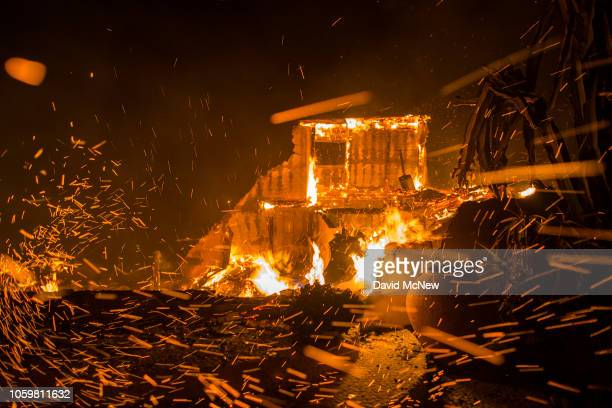 Strong winds blow embers from burning houses during the Woolsey Fire on November 9 2018 in Malibu California After a experiencing a mass shooting...