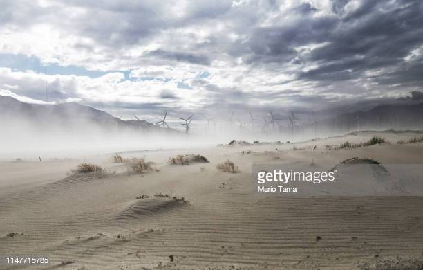 Strong winds blow sand at a wind farm in the Coachella Valley on May 6 2019 in Palm Springs California California's Fourth Climate Change Assessment...