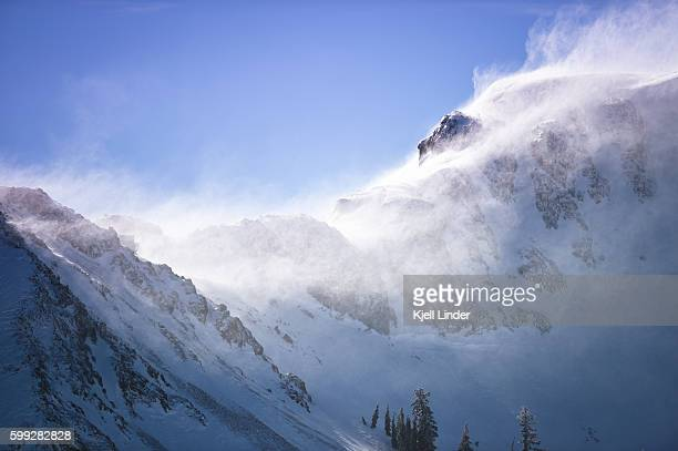 Strong winds blow snow off the side of a rugged mountain