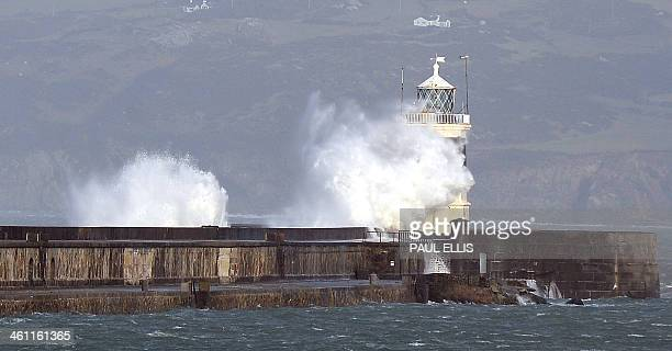 Strong winds cause the waves to hit the breakwater lighthouse at Holyhead on the Island of Anglesey in Wales on January 7, 2014. AFP PHOTO / PAUL...