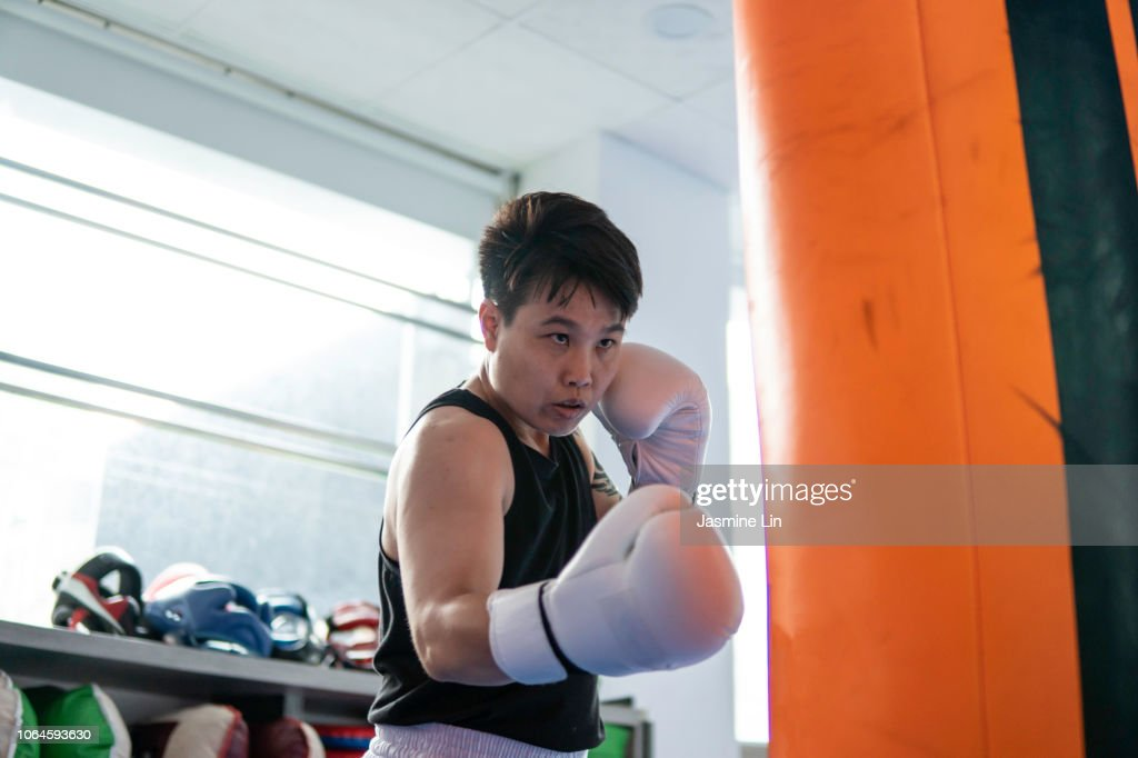 Strong woman boxer and punching bag
