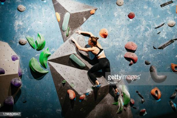 strong woman climbing on boulder wall, wide angle photo - chalk rock stock pictures, royalty-free photos & images