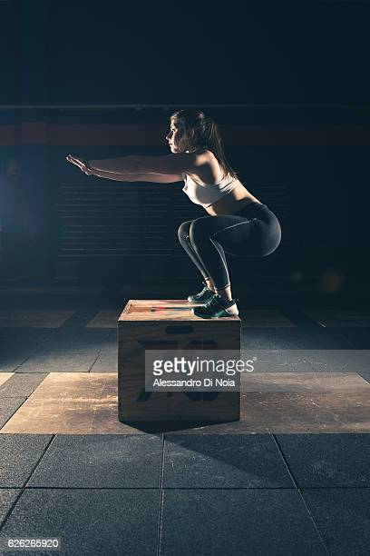 Strong woman jump on a crate in a gym