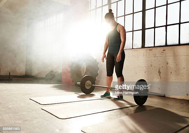 Strong woman preparing for weight training in gym