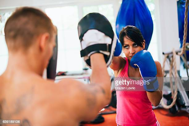 Strong woman punching and training with instructor