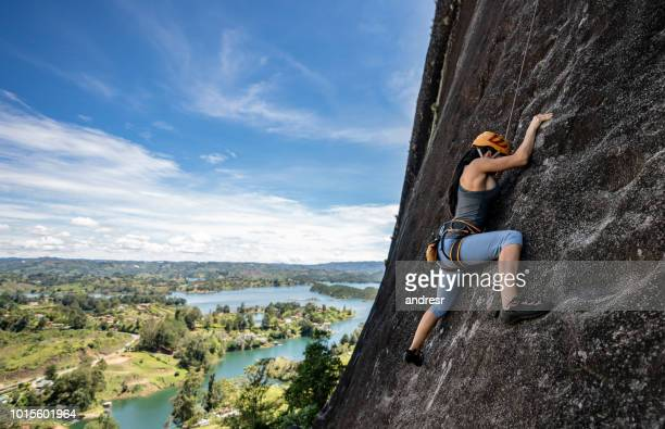strong woman rock climbing at guatape in colombia - rock climbing stock pictures, royalty-free photos & images