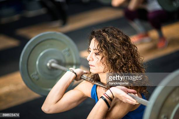 strong woman weightlifting a barbell - snatch weightlifting stock photos and pictures
