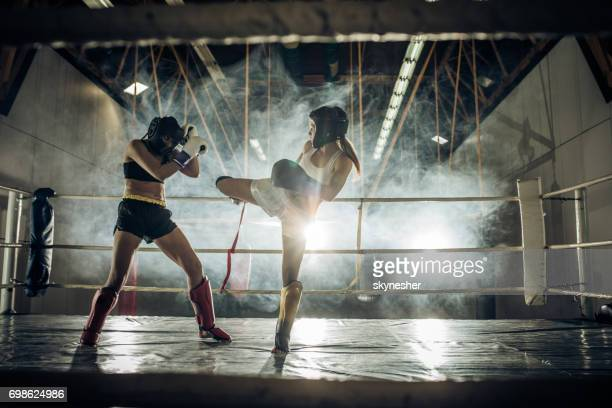 Strong women fighting on a kickboxing training in a ring.