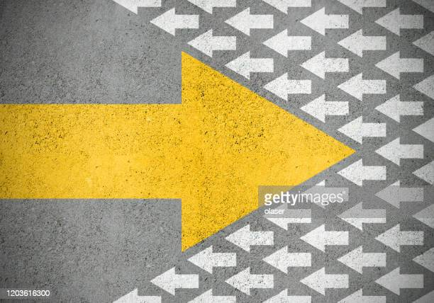 freccia gialla forte (idea) contro il vecchio bianco più piccolo (metodi) - cambiamento foto e immagini stock