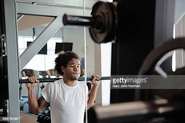 Strong young athlete lifting weights