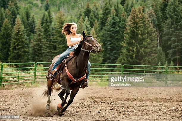 Strong young female riding a horse.