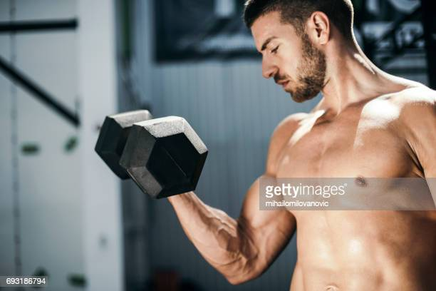 Strong young man does exercises