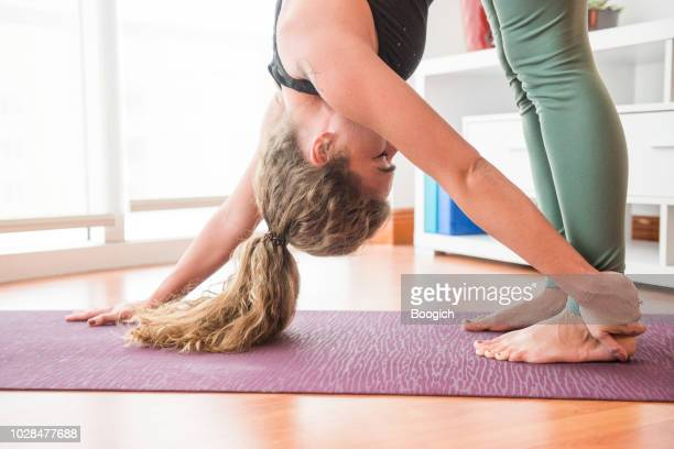 strong young woman holds one arm downward dog yoga pose at home in miami usa - yogi stock photos and pictures