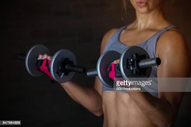 重みを持ち上げる強い若い女性 - 指なし手袋 ストックフォトと画像