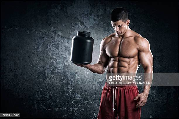 Strongman with can of supplements
