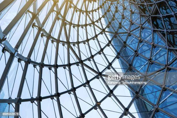 structural glass facade curving roof of fantastic office building at the center of bangkok's building - man made structure stock pictures, royalty-free photos & images