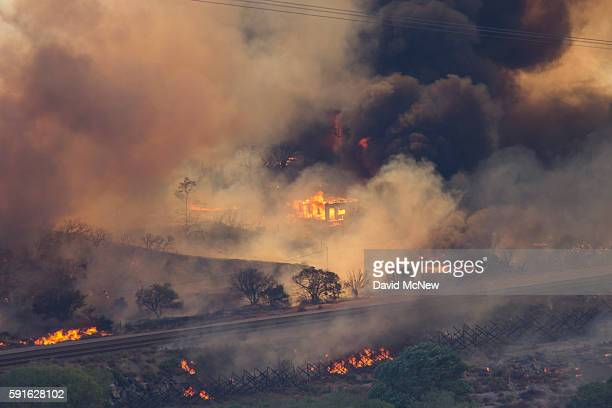 A structure burns as flames sweep through a rural community at the Blue Cut Fire on August 17 2016 near Wrightwood California An unknown number of...