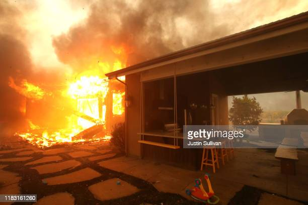 A structure continues to burn after the Kincade Fire moved through the area on October 24 2019 in Geyserville California Fueled by high winds the...