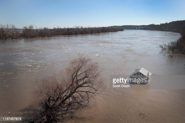 A structure is surrounded by floodwater on March 21 2019 in Atchison Kansas Several Midwest states are battling some of the worst flooding they have...