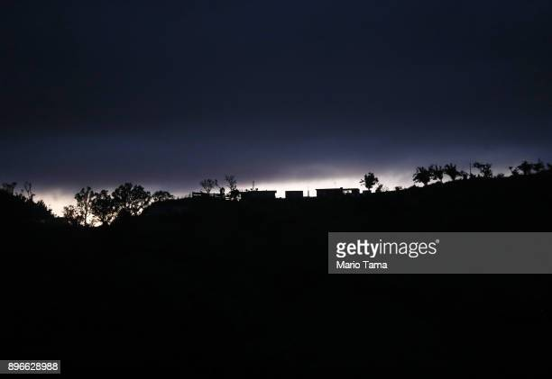 Structures and trees line a section of a populated ridge normally lit with electricity as dusk falls on December 20 2017 in Morovis Puerto Rico...