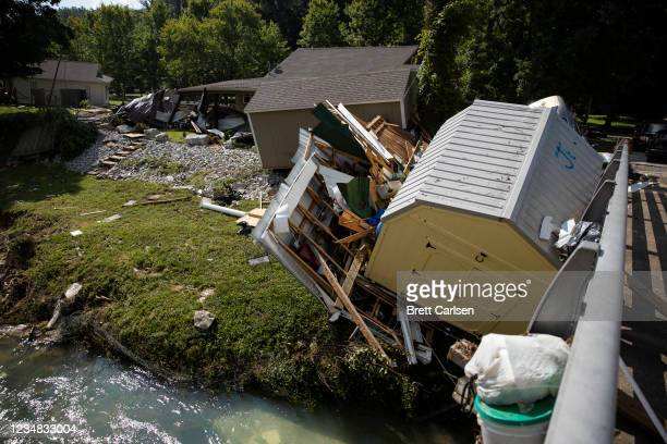 Structures and vehicles are piled up against a bridge over Trace Creek on August 23, 2021 in Waverly, Tennessee. Heavy rains on Sunday caused flash...