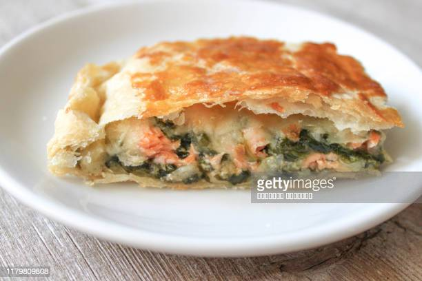 strudel pie with salmon and spinach on white plate served on wooden table - comida salgada - fotografias e filmes do acervo