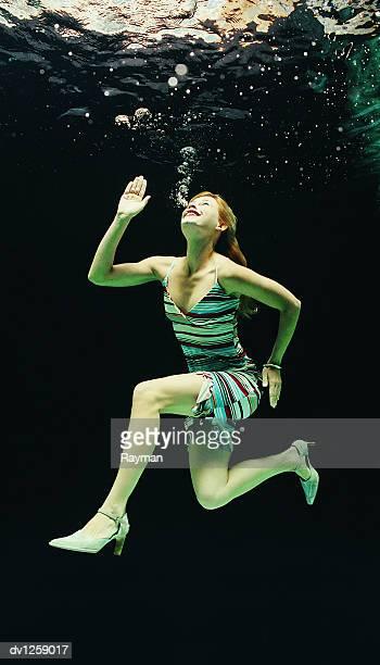 Struggling Businesswoman Trapped Underwater Looking Upwards