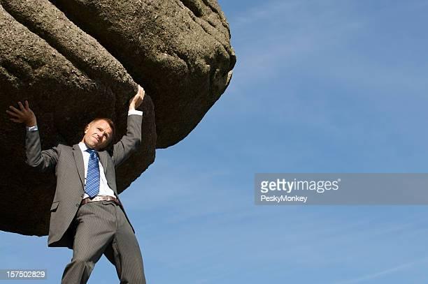 Struggling Strong Businessman Holding Huge Rock Boulder into the Sky