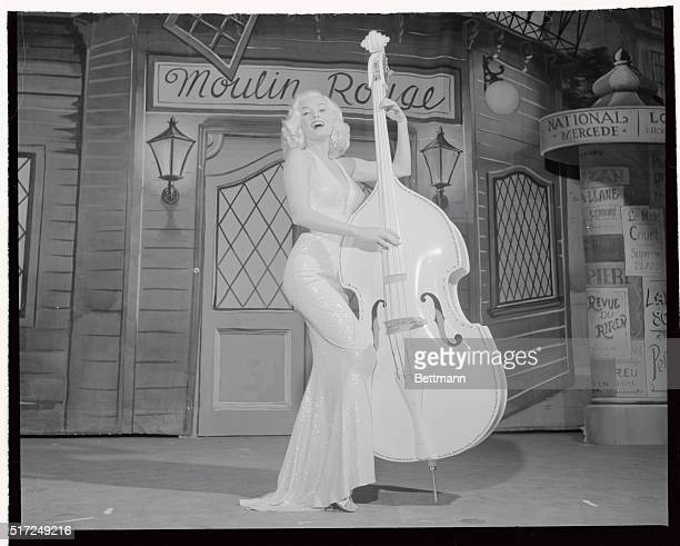 Strumming a bass fiddle trimmed with rhinestones to match her $12000 gown actress Mamie Van Doren sings Teddy Bear during her first night club...