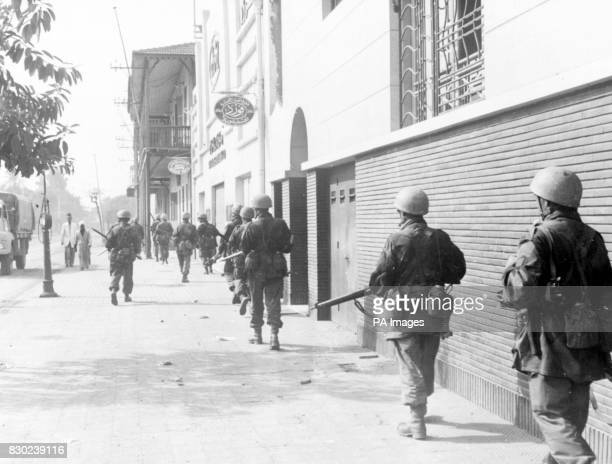 Strung out close to the buildings an Allied patrol moves through an almost deserted street in Port Said key town at the northern end of the Suez...