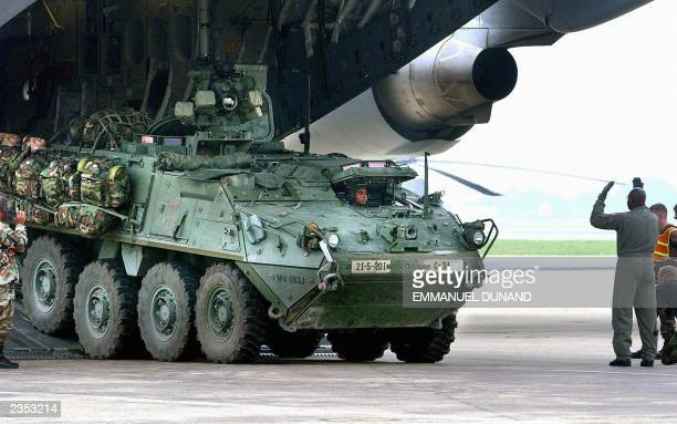 A Stryker infantry carrier vehicle the US Army's newest light armored vehicle is unloaded from a Hercules C17 military transport plane 31 July 2003...
